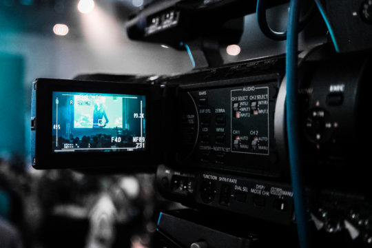 A Top Pup Media professional films a live event video production with his professional camera. The image is a close-up of the video camera's flip-screen.