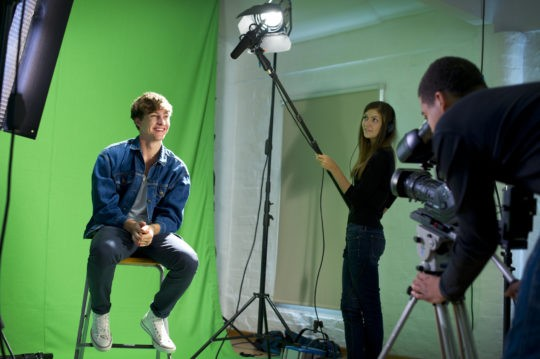 Staff from Top Pup Media films a student in front of a green screen for some education videos.