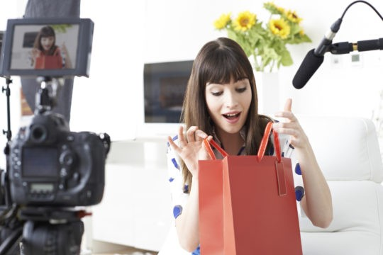 A girl is filmed examining a red purse. Top Pup Media recommends retail videos like this one to help your brand.